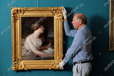 Stock Image of Charlie Wallrock with the painting at Wick Antiques in Lymington.  A lost portrait of Admiral Lord Nelson's mistress Lady Hamilton has been unearthed in an antiques shop.   The painting by Richard Westall shows Emma Hamilton gazing over her left shoulder, with her right breast exposed from under a loose gown.  It is thought to have been painted in 1802, three years before Nelson's death at the Battle of Trafalgar while defeating the combined French and Spanish fleets.  The painting in oil on canvas and mounted in a gold frame was taken to antique dealer in Lymington, Hants, by an eldelry woman who had owned it for years. It is now for sale for £85,000.