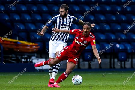 Bobby Reid of Fulham takes on Charlie Austin of West Bromwich Albion