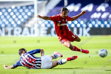 Bobby Reid of Fulham is fouled by Charlie Austin of West Bromwich Albion