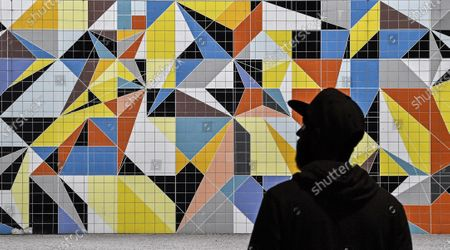 Man passes a colorful tiled mural by American artist Sarah Morris in the old town of Duesseldorf, Germany