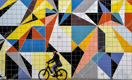 Stock Picture of Cyclist passes a colorful tiled mural by American artist Sarah Morris in the old town of Duesseldorf, Germany