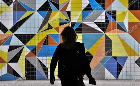 Woman passes a colorful tiled mural by American artist Sarah Morris in the old town of Duesseldorf, Germany