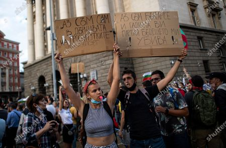 Young people hold up signs reading 'I am a Bulgarian and the nasty party is killing my future' during an anti-government protest in front of the Council of Ministers in Sofia, Bulgaria, 14 July 2020. Thousands of Bulgarians gathered in downtown Sofia for another day in support of President Rumen Radev, who called on the prime minister's 'mafia'-style government to resign amid claims of corruption after police raids on the president's offices, reports state.