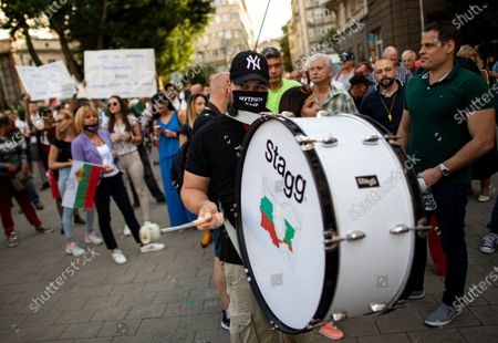A man beats the drum during an anti-government protest in front of the Council of Ministers in Sofia, Bulgaria, 14 July 2020. Thousands of Bulgarians gathered in downtown Sofia for another day in support of President Rumen Radev, who called on the prime minister's 'mafia'-style government to resign amid claims of corruption after police raids on the president's offices, reports state.