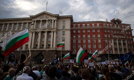 People wave national flags during an anti-government protest in front of the Council of Ministers in Sofia, Bulgaria, 14 July 2020. Thousands of Bulgarians gathered in downtown Sofia for another day in support of President Rumen Radev, who called on the prime minister's 'mafia'-style government to resign amid claims of corruption after police raids on the president's offices, reports state.