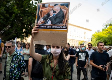 A women holds up a picture of Bulgarian Prime Minister Boyko Borissov during an anti-government protest in front of the Council of Ministers in Sofia, Bulgaria, 14 July 2020. Thousands of Bulgarians gathered in downtown Sofia for another day in support of President Rumen Radev, who called on the prime minister's 'mafia'-style government to resign amid claims of corruption after police raids on the president's offices, reports state.