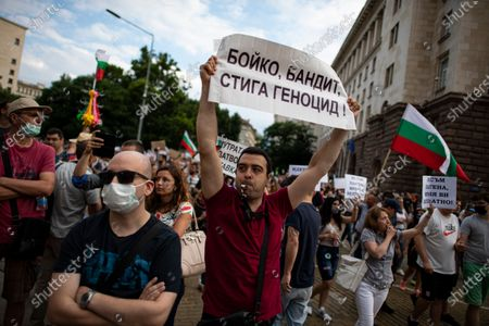 A man holds up a sign reading 'Boyko, bandit, enough genocide' during an anti-government protest in front of the Council of Ministers in Sofia, Bulgaria, 14 July 2020. Thousands of Bulgarians gathered in downtown Sofia for another day in support of President Rumen Radev, who called on the prime minister's 'mafia'-style government to resign amid claims of corruption after police raids on the president's offices, reports state.