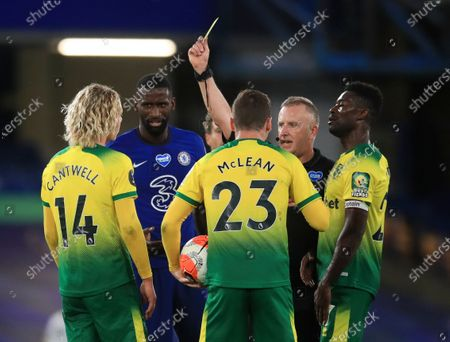 Norwich City's Todd Cantwell, left, is shown a yellow card by referee Jon Moss after fouling Chelsea's Ruben Loftus-Cheek during the English Premier League soccer match between Chelsea and Norwich City at Stamford Bridge in London, England