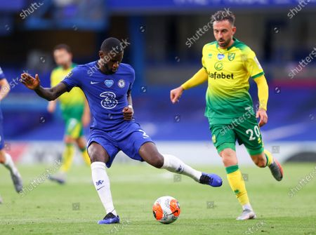Chelsea's Antonio Rudiger, left,kicks the ball as Norwich City's Josip Drmic watches during the English Premier League soccer match between Chelsea and Norwich City at Stamford Bridge in London, England