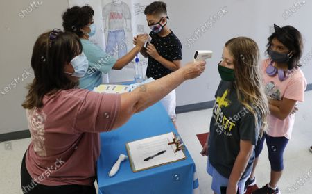 Amid concerns of the spread of COVID-19, science teachers Ann Darby, left, and Rosa Herrera check-in students before a summer STEM camp at Wylie High School, in Wylie, Texas