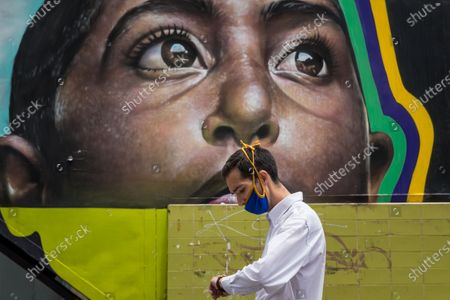 A man with a mask walks in front of a mural in Caracas, Venezuela, 14 July 2020. Caracas and the nearby state of Miranda will re-enter a 'radical quarantine' to stop the spread of the new coronavirus, only after two days of easing in other regions, Venezuelan Vice President Delcy Rodriguez reported on Tuesday.