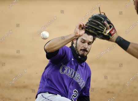 Colorado Rockies' Nolan Arenado, left, slides safely into third base as third baseman Brendan Rogers fields the throw during a simulated game as part of the team's practice, in Denver