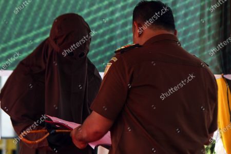 An officer hands over rattan to the executioner as a whip punishment tool for those that violate Islamic Sharia law in North Aceh District. Islamic Sharia Court in North Aceh dropped 74 lashes on convicted cases of sexual abuse of minors, lashing was carried out in accordance with the Covid-19 health protocols of using face shields and masks.