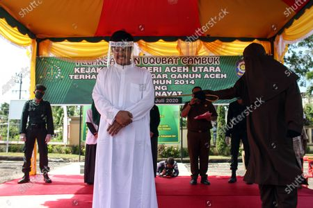 Stock Photo of The executioner seen whipping a man wearing a face shield for violating Islamic Sharia law in North Aceh District. Islamic Sharia Court in North Aceh dropped 74 lashes on convicted cases of sexual abuse of minors, lashing was carried out in accordance with the Covid-19 health protocols of using face shields and masks.