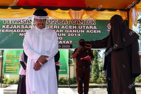 Stock Image of The executioner seen whipping a man wearing a face shield for violating Islamic Sharia law in North Aceh District. Islamic Sharia Court in North Aceh dropped 74 lashes on convicted cases of sexual abuse of minors, lashing was carried out in accordance with the Covid-19 health protocols of using face shields and masks.