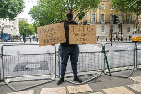 Protesters outside Downing Street carry placards with the names of the victims whi have died  for covid-19  and urging the government to take stronger action to combat the spread of coronavirus