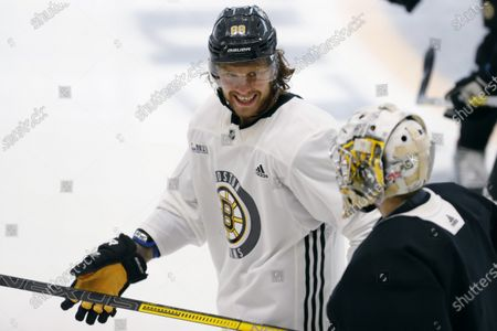 Boston Bruins right wing David Pastrnak jokes with goalie Daniel Vladar as they skate to the bench at the NHL hockey team's camp, in Boston