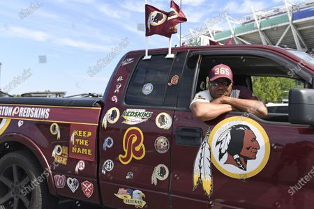 "Rodney Johnson of Chesapeake, Va., poses in his truck outside FedEx Field in Landover, Md., . The Washington NFL franchise announced Monday that it will drop the ""Redskins"" name and Indian head logo immediately, bowing to decades of criticism that they are offensive to Native Americans"