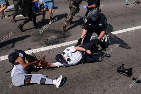 Black Lives Matter protester and NYPD officers scuffle on the Brooklyn Bridge during a demonstration, in New York. Several New York City police officers were attacked and injured Wednesday on the Brooklyn Bridge during a protest sparked by the death of George Floyd, police said. At least four officers were hurt, including the department's chief, and more than a dozen people were arrested