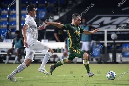 Portland Timbers midfielder Sebastian Blanco, right, attempts to kick a ball in front of LA Galaxy defender Daniel Steres (5) during the first half of an MLS soccer match, in Kissimmee, Fla