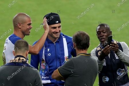 Porto former goalkeeper Iker Casillas, center with hat, joins the players celebrating on the pitch at the end of the Portuguese League soccer match between FC Porto and Sporting CP at the Dragao stadium in Porto, Portugal, . Porto defeated Sporting 2-0 to clinch the championship with two rounds left to play
