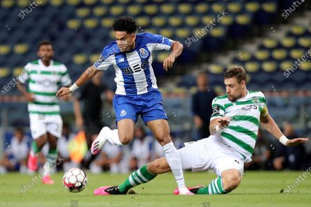 Sporting's Sebastian Coates, right, tackles Porto's Luis Diaz during the Portuguese League soccer match between FC Porto and Sporting CP at the Dragao stadium in Porto, Portugal, . The Portuguese League soccer matches are being played without spectators because of the coronavirus pandemic
