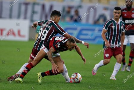 Fluminense's Evanilson, left, fights for the ball with Flamengo's Rafinha, center, during the Rio de Janeiro state championship final soccer match at the Maracana stadium, Rio de Janeiro, Brazil, . The match is being played without spectators to curb the spread of COVID-19