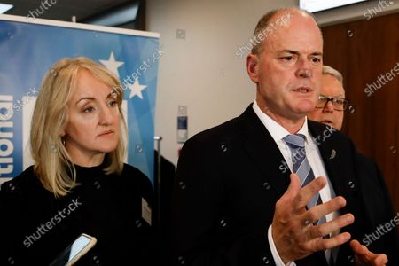 Amy Adams, left, former finance spokesperson for the opposition National Party, listens as former leader Todd Muller address the media in Christchurch, New Zealand, . The National Party suffered fresh setbacks ahead of a September election as two senior lawmakers announced their retirements. Days after the shock resignation of party leader Todd Muller, his deputy Nikki Kaye and former finance spokesperson Amy Adams said they will not seek reelection