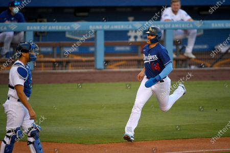 Los Angeles Dodgers' Enrique Hernandez, right, scores on a single by Max Muncy as catcher Austin Barnes stands at the plate during an intrasquad baseball game, in Los Angeles