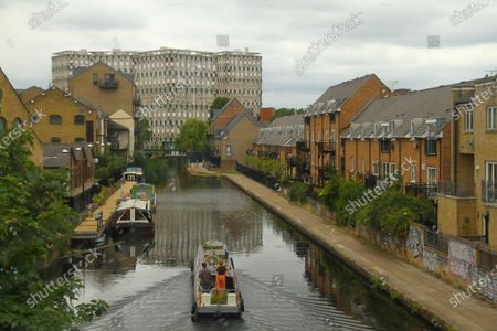 """People sailing on a boat through the Hertford Union canal  which runs parallel to part of Victoria Park in Hackney. Despite the reopening of """"non-essential"""" shops, parks and some leisure facilities, numbers of shoppers were still lower than usual as the public opt to purchase online and work from home."""