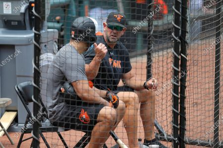 Baltimore Orioles right fielder Anthony Santander, left, talks with manager Brandon Hayes during baseball training camp, in Baltimore