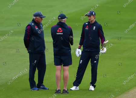 England's captain Joe Root, right, talks to head coach Chris Silverwood, left, and bowling coach Glen Chapple as rain delayed start of the first day of the second cricket Test match between England and West Indies at Old Trafford in Manchester, England