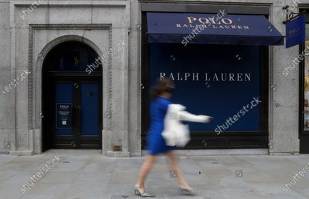 Woman walks by a closed Ralph Lauren store in London, . Unemployment across the U.K. has held steady during the coronavirus lockdown as a result of a government salary support scheme, but there are clear signals emerging that job losses will skyrocket over coming months. The Office for National Statistics said Thursday there were 649,000 fewer people, or 2.2%, on payroll in June when compared with March when the lockdown restrictions were imposed