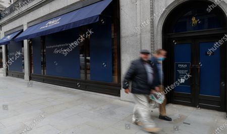 Men walk by a closed Ralph Lauren store in London, . Unemployment across the U.K. has held steady during the coronavirus lockdown as a result of a government salary support scheme, but there are clear signals emerging that job losses will skyrocket over coming months. The Office for National Statistics said Thursday there were 649,000 fewer people, or 2.2%, on payroll in June when compared with March when the lockdown restrictions were imposed