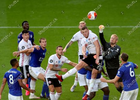Leicester's goalkeeper Kasper Schmeichel, right, makes a save in front of Sheffield United's Jack O'Connell during the English Premier League soccer match between Leicester City and Sheffield United at the King Power Stadium, in Leicester, England