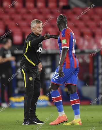 Manchester United's manager Ole Gunnar Solskjaer, left, greets Crystal Palace's Mamadou Sakho as he leaves the pitch at the end of the English Premier League soccer match between Crystal Palace and Manchester United at Selhurst Park in London, England, . United won the match 2-0