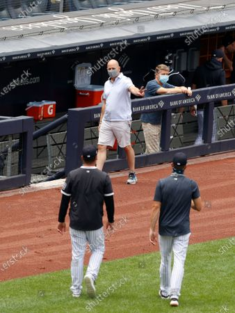 New York Yankees general manager Brian Cashman flashes a peace sign as he walks off the field past New York Yankees Owner / Managing general partner Hal Steinbrenner (R) during summer camp before the start of the 2020 MLB season at Yankee Stadium in the Bronx, New York, USA, 16 July 2020. The start of the season was delayed due to the outbreak of the coronavirus and COVID-19 disease pandemic.