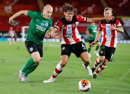 Brighton's Aaron Mooy, left, and Southampton's Jannik Vestergaard battle for the ball during the English Premier League soccer match between Southampton and Brighton at St. Mary's Stadium in Southampton, England