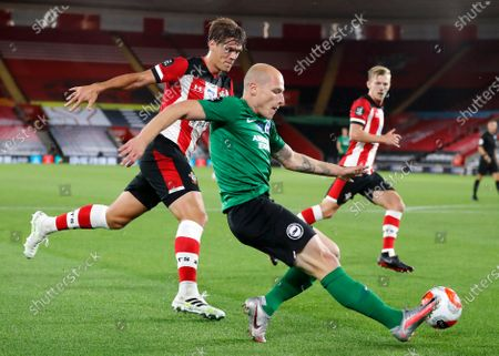 Brighton's Aaron Mooy kicks the ball away from Southampton's Jannik Vestergaard battle for the ball during the English Premier League soccer match between Southampton and Brighton at St. Mary's Stadium in Southampton, England