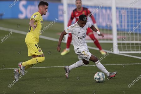 Real Madrid's Rodrygo, right, dribbles past Villareal's Xavi Quintilla, during the Spanish La Liga soccer match between Real Madrid and Villareal at the Alfredo di Stefano stadium in Madrid, Spain