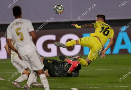 Real Madrid's goalkeeper Thibaut Courtois, bottom, blocks Villareal's Xavi Quintilla, right, during the Spanish La Liga soccer match between Real Madrid and Villareal at the Alfredo di Stefano stadium in Madrid, Spain