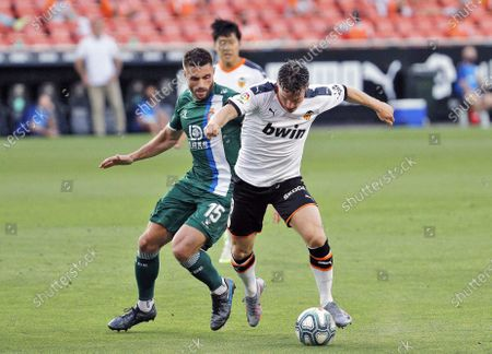 Valencia's Kevin Gameiro (R) in action against Espanyol's David Lopez (L) during the Spanish LaLiga soccer match between Valencia CF and RCD Espanyol held at Ciutat Mestalla Stadium, in Valencia, Spain, 16 July 2020.