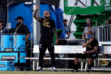 Montreal Impact coach Thierry Henry, left, gestures on the sideline during the first half of an MLS soccer match against Toronto FC, in Kissimmee, Fla