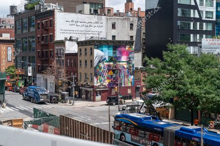 Mural by Eduardo Kobra portraying Mahatma Gandhi and Mother Teresa seen from High Line Park as it reopens to the public with limited capacity after temporarily closed in March amid Covid-19. Park is public however financed by private investments. Strict social distancing rules are in place and visitors have to reserve free timed-ticket in advance online. Wearing mask is mandatory and green dots are placed on the ground six feet apart to keep visitors separated. All visitors must start at the southern end of the park at Gansevoort Street and can only walk north up to 23rd Street, where they must exit, park will be closed beyond that point.