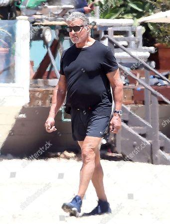 Sylvester Stallone walks on the beach in Malibu