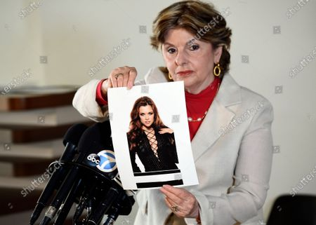 Attorney Gloria Allred holds up a 1990s picture of her client, model Alicia Arden, at a news conference at the Allred, Maroko & Goldberg law offices, in Los Angeles. Arden said she was sexually assaulted and battered by the late financier Jeffrey Epstein in 1997 at the Shutters on the Beach hotel in Santa Monica, Calif., but that she was never contacted by police or any prosecutor after filing a police report with the Santa Monica Police Dept