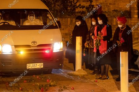 Mourners observe as an official vehicle carrying the late Zindzi Mandela, the daughter of the late Nelson Mandela, leaves her parents home in the township of Soweto in Johannesburg, South Africa, . Zindzi died at age of 59 in a Johannesburg hospital after a short illness. She was Nelson Mandela and Winnie Mandela's youngest daughter