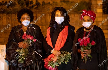 Stock Photo of Mourners observe as an official vehicle carrying the late Zindzi Mandela, the daughter of the late Nelson Mandela, leaves her parents home in the township of Soweto in Johannesburg, South Africa, . Zindzi died at age of 59 in a Johannesburg hospital after a short illness. She was Nelson Mandela and Winnie Mandela's youngest daughter