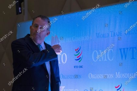 Candidate for Director General of the World Trade Organization (WTO), Liam Fox from United Kingdom, takes off his prospective mask as a precaution against the spread COVID-19 prior the press conferences of candidates for the WTO Director-General selection process, at the headquarters of the World Trade Organization (WTO) in Geneva, Switzerland, 17 July 2020.