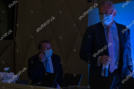 Candidate for Director General of the World Trade Organization (WTO), Liam Fox (L) from United Kingdom, takes off his prospective mask as a precaution against the spread COVID-19 next to WTO Spokesperson Keith Rockwell (R) prior the press conferences of candidates for the WTO Director-General selection process, at the headquarters of the World Trade Organization (WTO) in Geneva, Switzerland, 17 July 2020.